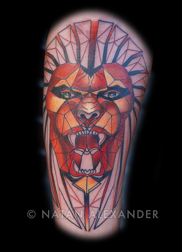 Arm tattoo in color ink of geometric lion head by Natan Alexander