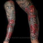 Full sleeve left arm tattoo in color ink of a skull and red roses with beads by Natan Alexander