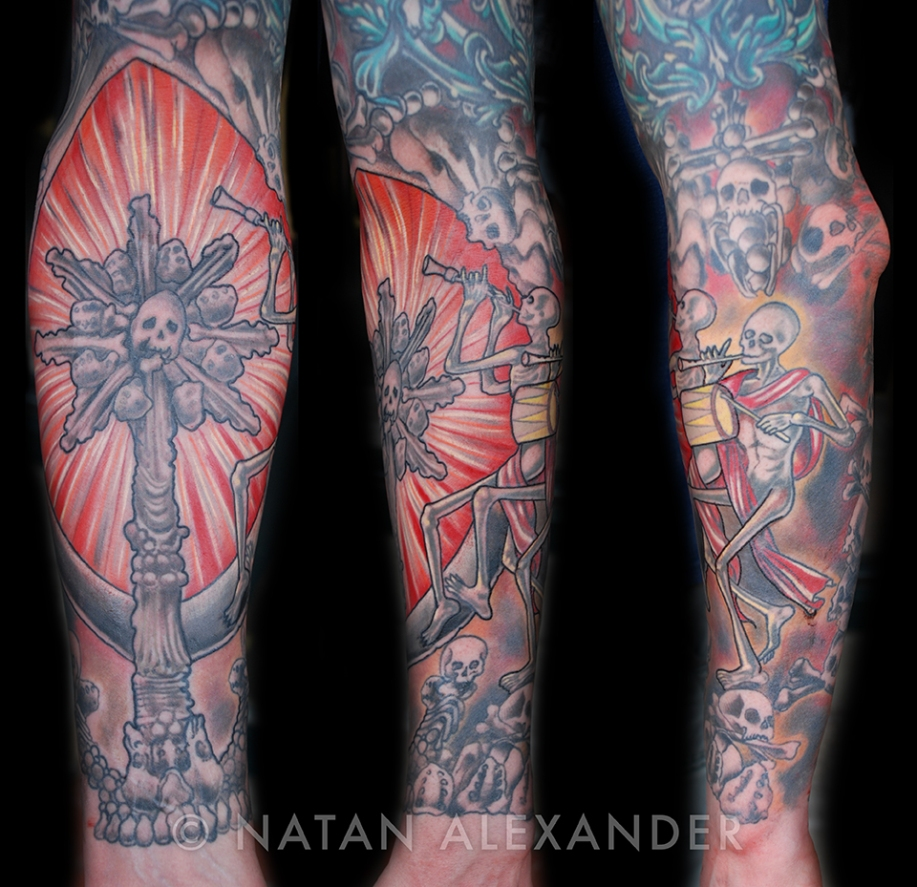 Full sleeve arm tattoo in color ink of skulls and skeletons playing music instruments by Natan Alexander