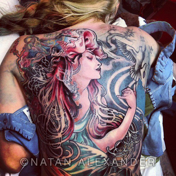 A woman showing her bare back with a full tattoo an Alphonse Mucha art nouveau lady with flowing hair near a flying dove in color ink by Natan Alexander.