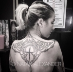 Upper back tattoo with a filigree lace design around a sketched cross in black ink by Natan Alexander
