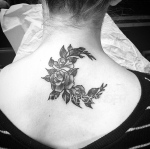 Upper center back tattoo of roses and leaves forming a crescent moon shape in black and gray ink by Natan Alexander
