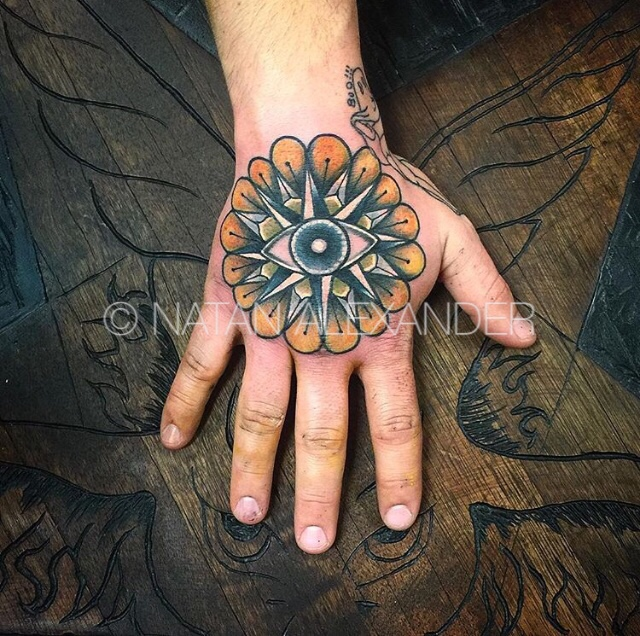 Hand tattoo of open eye over nautical star points and orange petals in color ink by Natan Alexander