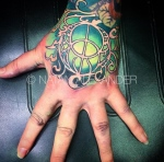 Hand tattoo featuring an ornamental green goddess charm in color ink by Natan Alexander.
