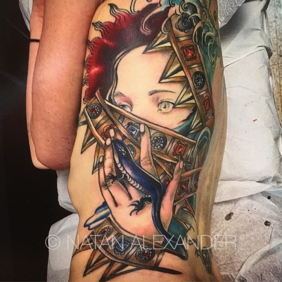 Color ink torso tattoo of a woman's face half covered by gold metal bands with faceted gems and a blue lizard by Natan Alexander.