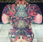 Full back color ink tattoo of wings comprised of scroll design wih alchemical sacred geometry by Natan Alexander.