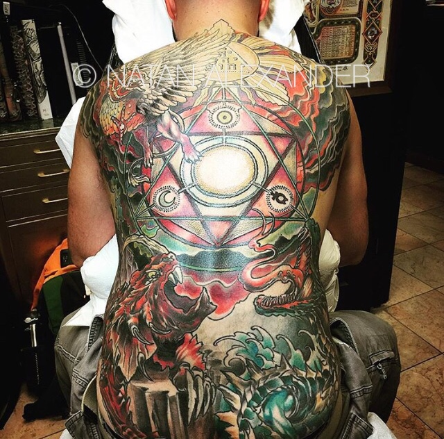 Full back color ink tattoo of a dramatic Battle of Revelation scene with sun, ocean, creatures, and sacred geometry by Natan Alexander.
