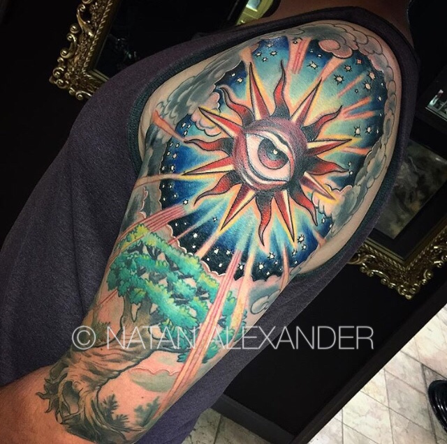 Arm with tattoo of a shining sun with an open protective eye at the center surrounded by clouds above a tree in color ink by Natan Alexander