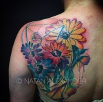 Back tattoo of watercolor daisies in rainbow colors with a Fibonacci spiral in color ink by Natan Alexander