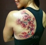 Woman smiling with a back tattoo of a cherry blossom branch woth red and pink flowers blooming in black and color ink by Natan Alexander