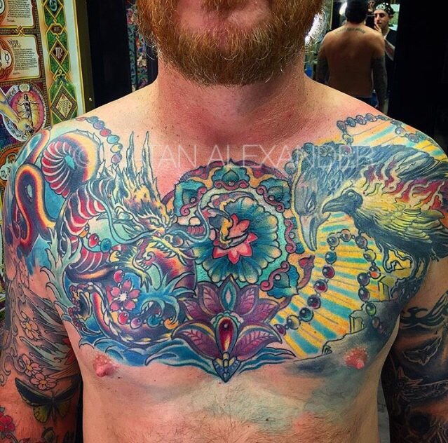 Colorful chest tattoo of a Chinese dragon and ravens with jeweled lotus in color ink by Natan Alexander