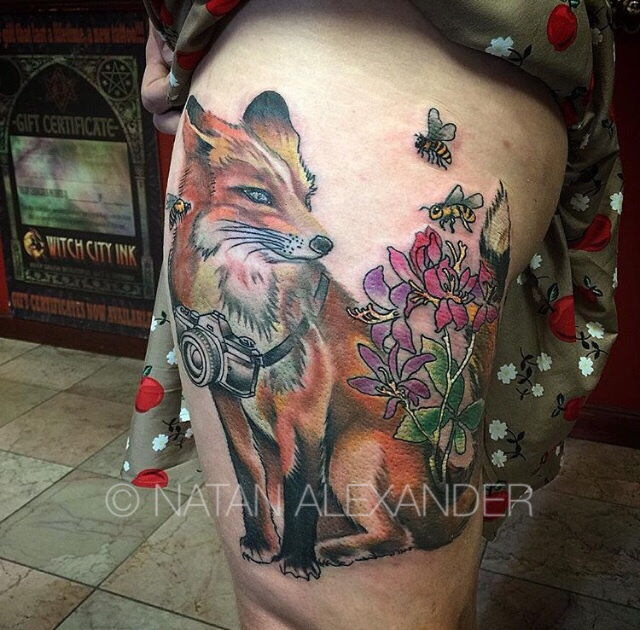 Thigh tattoo of an orange fox wearing a camera standing near pink and purple flowers and flying bees in color ink by Natan Alexander