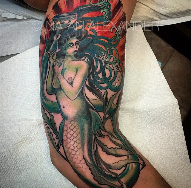 Tattoo of teal green mermaid holding a chalice with astrological symbols surrounded by seaweed in color ink by Natan Alexander