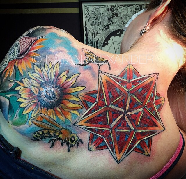 Upper back tattoo of complex sacred geometry and bees flying over sunflowers in color ink by Natan Alexander