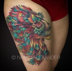 Thigh tattoo of a colorful lion head profile in deep reds, oranges, yellows, and turquoises in color ink by Natan Alexander